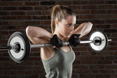 Young fit woman lifting dumbbells on brick background Stock Photo