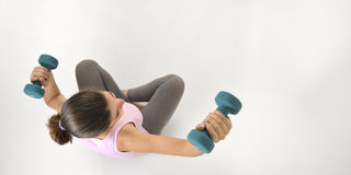 Young fit woman lifting dumbbells stock photo