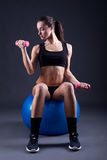 Young fit woman lifting dumbell on black background Royalty Free Stock Image