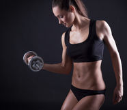 Young fit woman lifting dumbell on black background Stock Photo