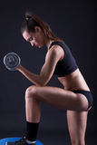 Young fit woman lifting dumbell on black background Royalty Free Stock Images