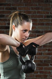 Young fit woman lifting kettle bell on brick background Royalty Free Stock Images