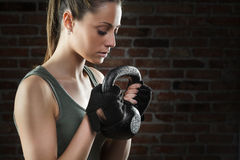 Young fit woman lifting kettle bell on dark background Royalty Free Stock Image