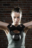 Young fit woman lifting kettle bell and looking at camera Stock Photography