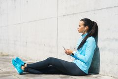 Young, fit and sporty girl in the street. Fitness, sport, urban jogging and healthy lifestyle concept. Stock Photography