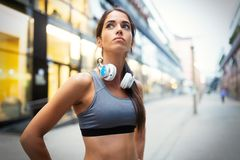 Young fit woman listening to music and working out by running. In city royalty free stock images