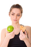 Young fit woman making decision what to eat Royalty Free Stock Photo