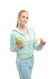 A young and fit woman measuring a green apple Stock Image