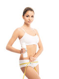 A young and fit woman measuring her hips with a tape Royalty Free Stock Photo