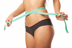 Young fit woman measuring her waistline Stock Images