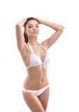A young and fit woman posing in a white swimsuit Royalty Free Stock Photography