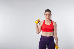 Young fit woman posing with yellow dumbbells stock photos