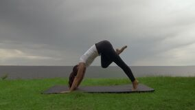 Young fit woman practice yoga on coast near the lake or sea. Woman doing Three Legged Downward-Facing Dog then Warrior