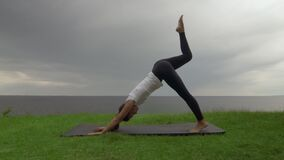 Young fit woman practice yoga on coast near the lake or sea. Woman doing Three Legged Downward-Facing Dog then Warrior I