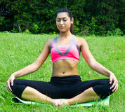 Young fit woman practices yoga in the park to meditate and relax Stock Photos