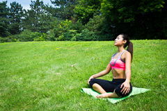 Young fit woman practices yoga in the park to meditate and relax Royalty Free Stock Photography