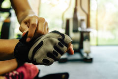 Young fit woman putting his gloves Royalty Free Stock Photography
