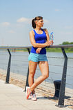 Young fit woman resting after jogging by the river in city. Stock Photos