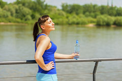 Young fit woman resting after jogging by the river in city. Royalty Free Stock Photos