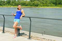 Young fit woman resting after jogging by the river in city. Stock Photo