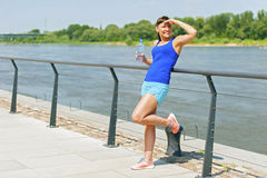 Young fit woman resting after jogging by the river in city. Hand Stock Photos
