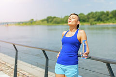 Young fit woman resting after jogging by the river in city. Royalty Free Stock Photography