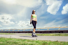 Young and fit woman rollerblading on skates royalty free stock photography