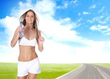 A young and fit woman is running with a bottle Royalty Free Stock Photography