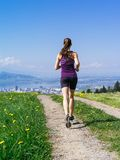 Young fit woman running down gravel road Royalty Free Stock Photo