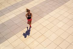 Young fit woman running in sunny day in the city Stock Images
