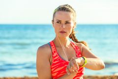 Young fit woman on seacoast setting fitness bracelet Royalty Free Stock Image
