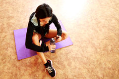 Young fit woman sitting on the yoga mat Royalty Free Stock Images