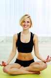 Young fit woman sitting on the yoga mat and meditates Royalty Free Stock Photography