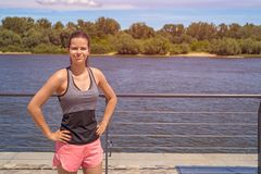 Young fit woman smiling at camera outdoor by the river. Royalty Free Stock Images