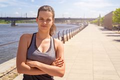 Young fit woman in sportswear standing with crossed arms in the Stock Photography
