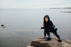 Young fit woman stand on rocks and rest after a hard workout. Stock Image