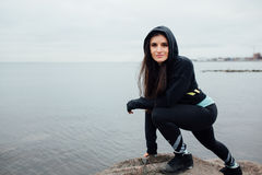 Young fit woman stand on rocks and rest after a hard workout. Stock Photography