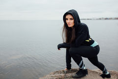 Young fit woman stand on rocks and rest after a hard workout. Motivation, sport and fitness lifestyle concept. Whater background Stock Images