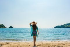 Young fit woman standing on a tropical beach in the summer vacation. Full length rear view of a young fit woman standing on a tropical beach against a clear blue Royalty Free Stock Photos