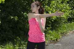 Young fit woman  stretching her arm on a sunny day outdoors in n Stock Image