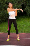 Young fit woman stretching in shade outdoor on summer afternoon Royalty Free Stock Images