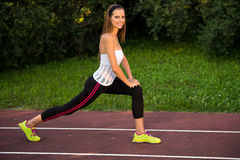 Young fit woman stretching in shade outdoor on summer afternoon Royalty Free Stock Image