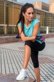 Young fit woman taking a break after exercising or running. Fitness girl standing and resting outdoors on city street. Royalty Free Stock Photo