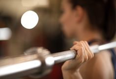 Young woman training with barbell in gym Royalty Free Stock Images