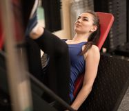 Young fit woman training legs in gym Stock Photo