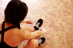 Young fit woman tying her shoelaces Royalty Free Stock Images