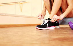 Young fit woman tying her shoelaces Royalty Free Stock Image