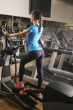 Young fit woman using an elliptic trainer in a fitness center, back shot. Portrait of fitness girl in the gym, lifestyle concept.. Young fit woman using an Stock Photos