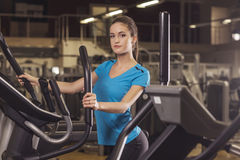 Young fit woman using an elliptic trainer in a fitness center, back shot. Portrait of fitness girl in the gym. Young fit woman using an elliptic trainer in a Stock Image