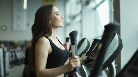 Young fit woman using an elliptic trainer in a fitness center. A group of young women train on sports training equipment in a fitness gym. Steady cam shot stock video